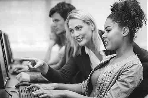 El profesor de Marketing que apunta a un estudiante de la pantalla de la computadora durante una lección sobre el texto alt